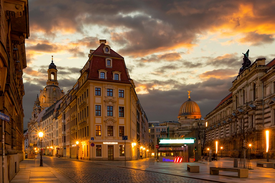 Buildings in Dresden, Germany are softly lit against a setting sun and partially cloudy sky.
