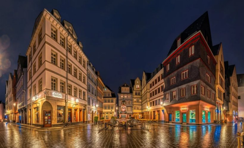 Historic buildings in Frankfurt, Germany reflect off rain-soaked streets at night.